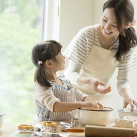 キッチンでお菓子作りをする親子