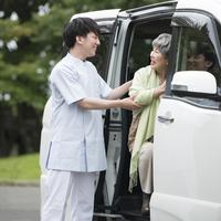 車に乗るシニア女性を支える介護士