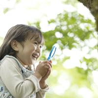 虫眼鏡を持ち微笑む女の子 11017016625| 写真素材・ストックフォト・画像・イラスト素材|アマナイメージズ