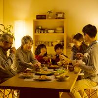 夕食を食べる3世代家族