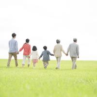 草原を歩く3世代家族の後姿