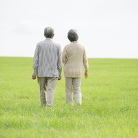 草原を歩くシニア夫婦の後姿