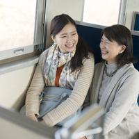 電車の中で談笑をする親子