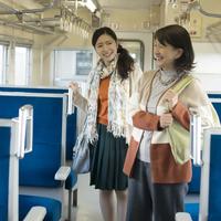 電車の中を歩く親子