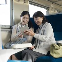 電車の中でタブレットPCを見る親子