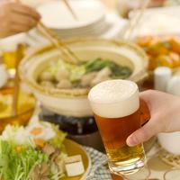 ビールを持つ手と鍋料理