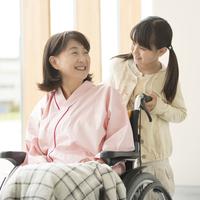 祖母の車椅子を押す女の子