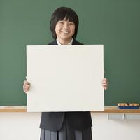 メッセージボードを持ち微笑む女子学生