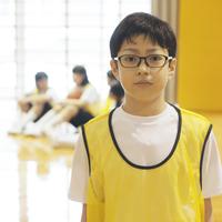 体育館で真剣な表情をする男子学生