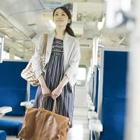 電車の通路を歩く女性