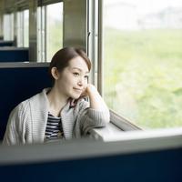 電車に乗り景色を眺める女性