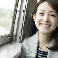 電車の中で微笑む女性