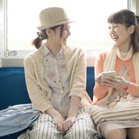 電車の中で談笑をする2人の女性 11017019736  写真素材・ストックフォト・画像・イラスト素材 アマナイメージズ