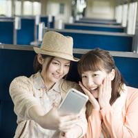 スマートフォンで自分撮りをする2人の女性 11017019766  写真素材・ストックフォト・画像・イラスト素材 アマナイメージズ