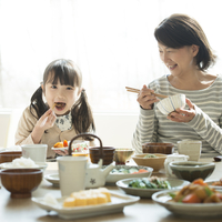 朝食を食べる女の子と祖母 11017020234| 写真素材・ストックフォト・画像・イラスト素材|アマナイメージズ