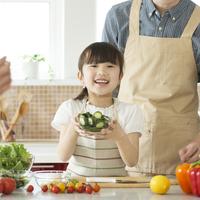 キッチンで切った野菜を持ち微笑む女の子 11017020295| 写真素材・ストックフォト・画像・イラスト素材|アマナイメージズ