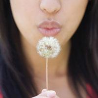 womans face blowing dandelion