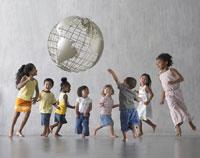 Group of children dancing around globe