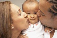 parents kissing babys cheeks