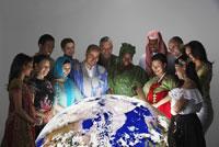 people in dress looking at globe