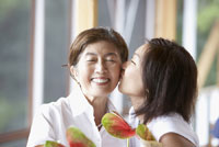 Asian woman kissing mother on cheek 11018016196  写真素材・ストックフォト・画像・イラスト素材 アマナイメージズ