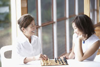 mother and adult daughter playing chess
