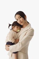 businesswoman hugging baby daughter