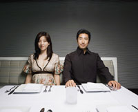 Asian couple sitting at restaurant