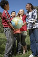 Multi-ethnic children holding globe