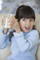 Hispanic girl shaking Christmas gift 11018022835| 写真素材・ストックフォト・画像・イラスト素材|アマナイメージズ