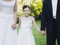 newlyweds holding flower girl�fs hands
