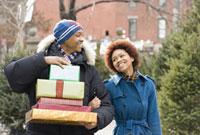 African man carrying stack of Christmas presents 11018030881  写真素材・ストックフォト・画像・イラスト素材 アマナイメージズ