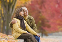 Hispanic couple sitting outdoors in autumn