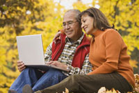 Hispanic couple using laptop sitting in autumn leaves