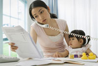 Asian mother working at home with baby 11018031475| 写真素材・ストックフォト・画像・イラスト素材|アマナイメージズ