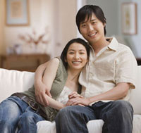 Asian couple hugging on sofa
