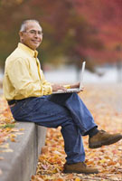 Hispanic man using laptop outdoors in autumn