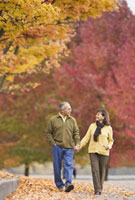 Hispanic couple holding hands outdoors in autumn