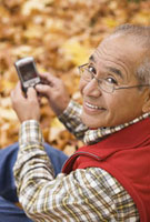 Hispanic man using cell phone outdoors in autumn