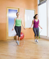 Two women jumping rope in health club