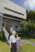 Portrait of middle-aged couple in front of house
