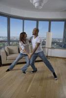 Multi-ethnic couple dancing in livingroom