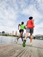 Couple running on urban boardwalk along river