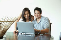 Japanese couple using laptop at table