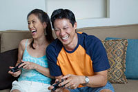 Japanese couple playing video games in living room