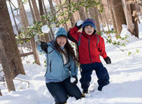 Japanese mother and son throwing snowballs