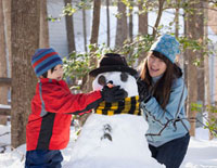 Japanese mother and son building snowman