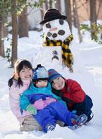 Japanese children sitting next to snowman