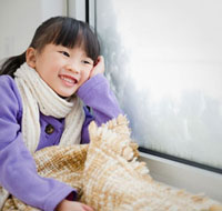 Chinese girl with blanket looking out window