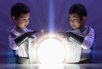 Korean brothers in superhero costumes looking at glowing orb